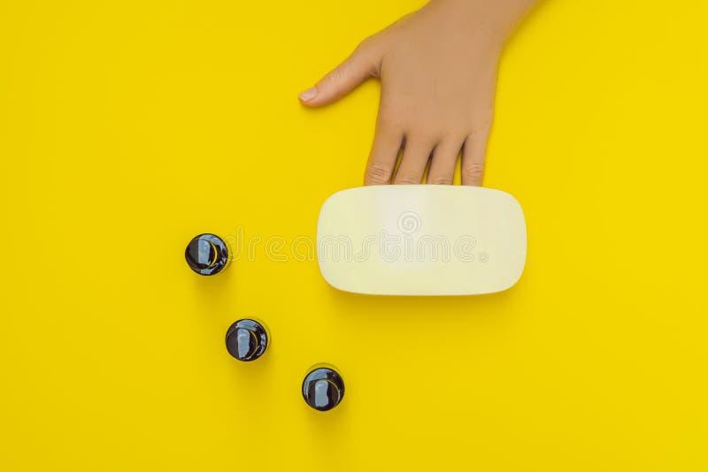 La femme remet le soin Ongles manucurés dans la lampe UV Poli de gel de traitement de rayons Petits art d'ongle et affaires de ma photo stock