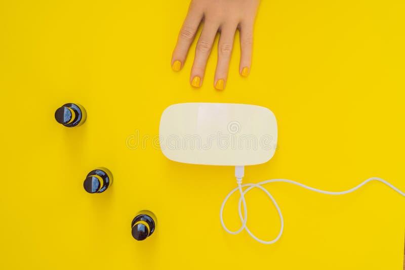 La femme remet le soin Ongles manucurés dans la lampe UV Poli de gel de traitement de rayons Petits art d'ongle et affaires de ma photos libres de droits