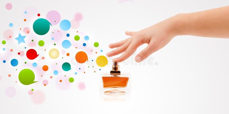 la femme remet les bulles colorées de pulvérisation de la belle bouteille de parfum images libres de droits