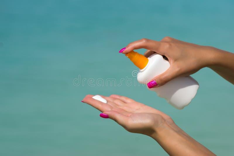 La femme remet mettre la protection solaire d'une bouteille de suncream photographie stock libre de droits