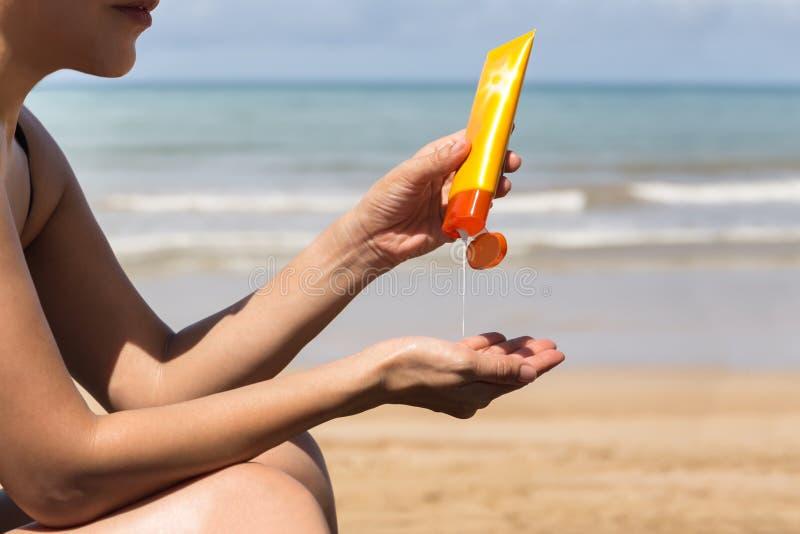 La femme remet mettre la protection solaire d'une bouteille de suncream photos stock