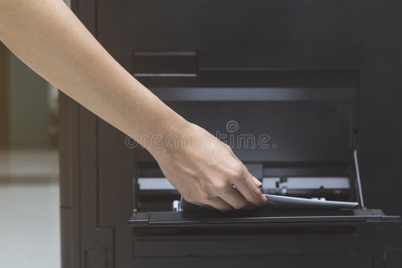 La femme remet mettre une feuille de papier dans un dispositif de copie images stock