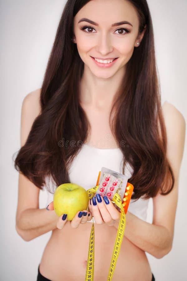 La femme remet tenir la boursouflure des pilules et des fruits images stock