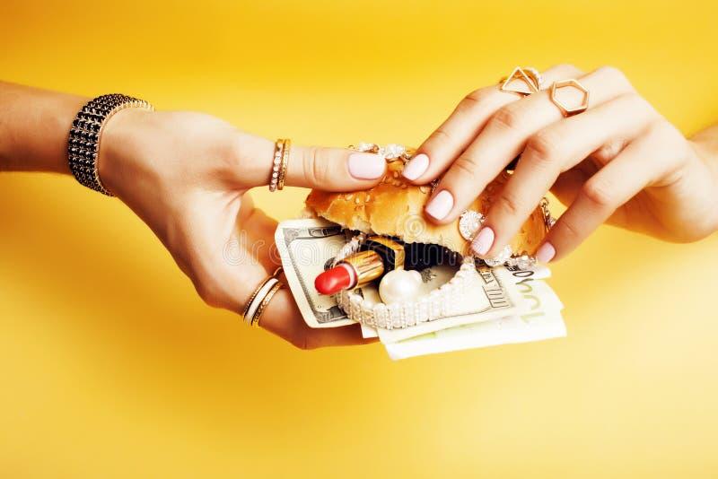 La femme remet tenir l'hamburger avec l'argent, bijoux, cosmétique, concept social de richesse de question photographie stock