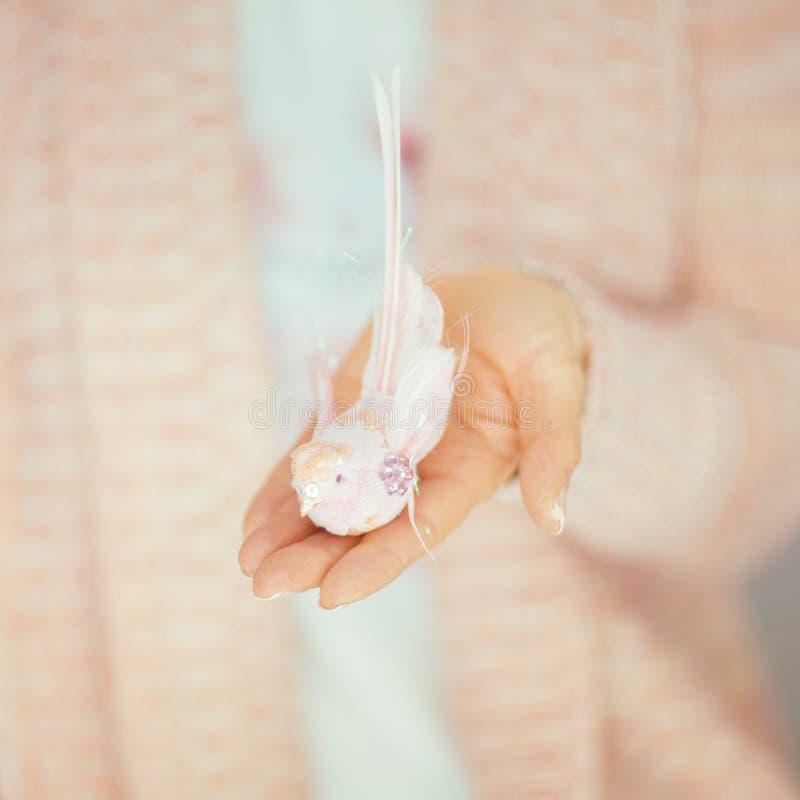 La femme remet tenir le petit oiseau artificiel dans des ses mains, couleurs en pastel rose-clair image stock