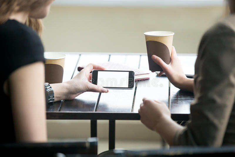 La femme remet tenir le téléphone avec l'écran vide blanc en café C image stock