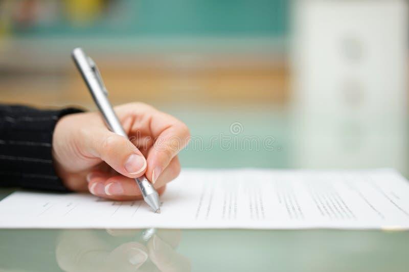 La femme remplit document sur la table en verre, profondeur de champ photos stock