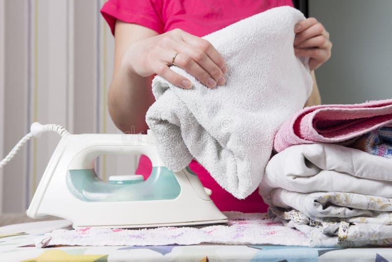 La femme repasse des serviettes sur la planche à repasser Femme au foyer avec du fer et la pile de la toile photos stock