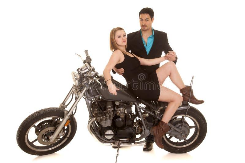 La femme reposent la jambe de moto vers le haut de l'homme derrière photographie stock libre de droits