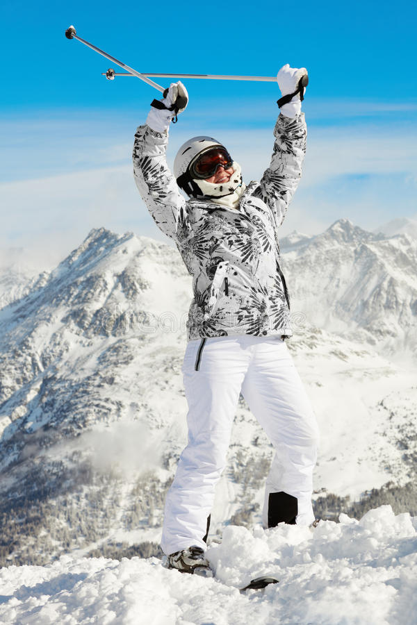La femme reste projetante vers le haut des mains avec des pôles de ski photos stock