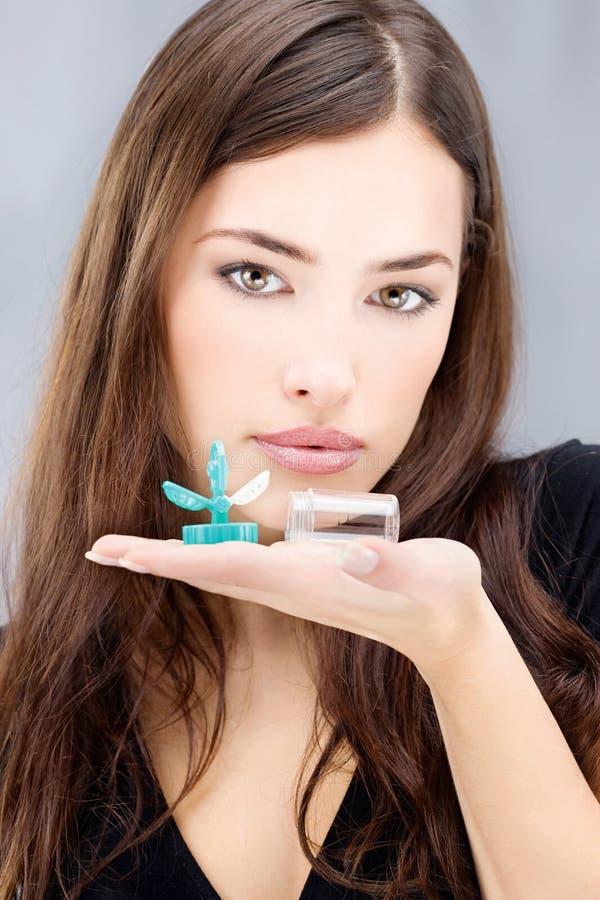 La femme retenant des verres de contact lavent le conteneur photo libre de droits