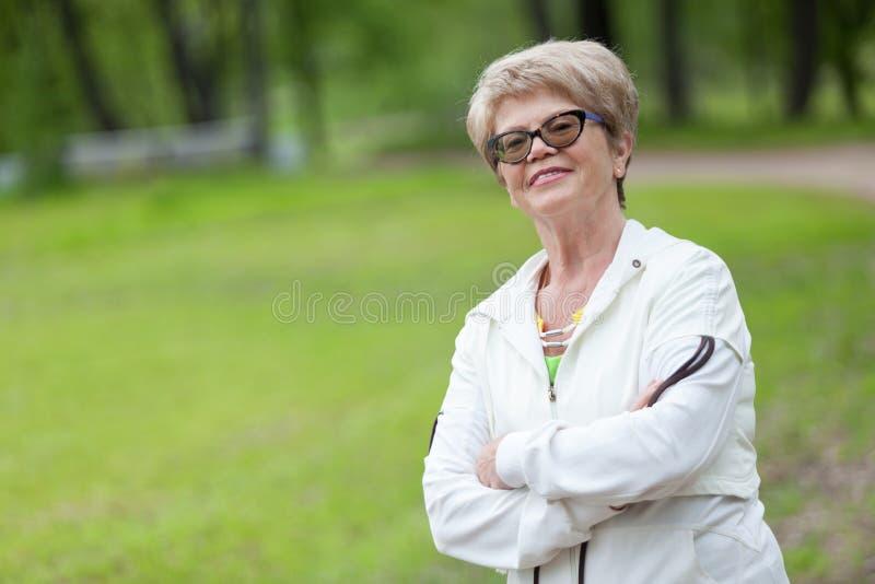 La femme retirée de bonne composition européenne se tient en parc d'été dans un costume de sports, l'espace de copie photographie stock libre de droits