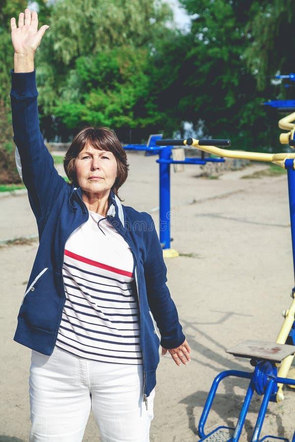 La femme retirée mignonne exécute des exercices gymnastiques sur la rue images libres de droits