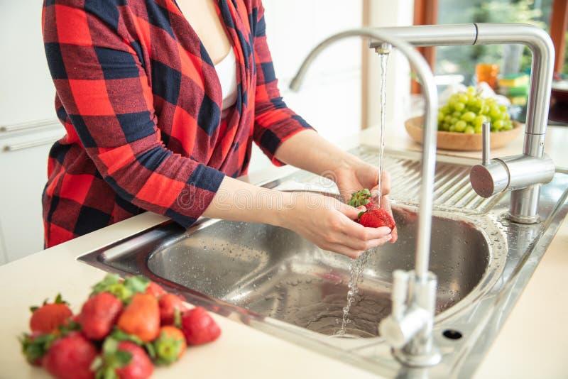 La femme rince les fraises dans la cuisine photo libre de droits