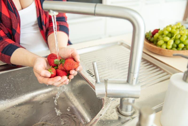 La femme rince les fraises dans la cuisine photos libres de droits