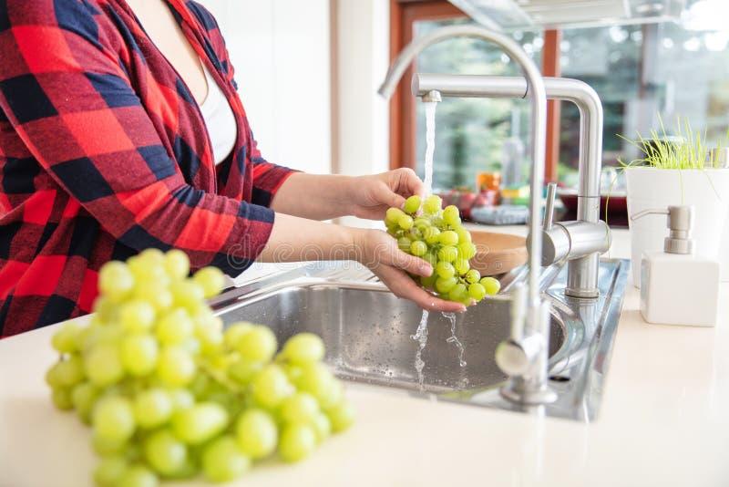 La femme rince les raisins verts avec de l'eau photos libres de droits