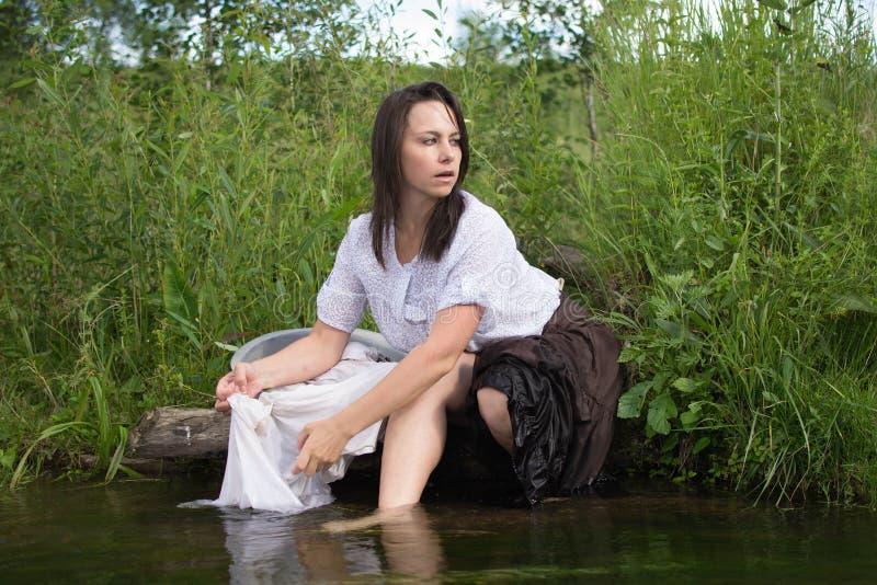 La femme rurale lave des vêtements en rivière photographie stock