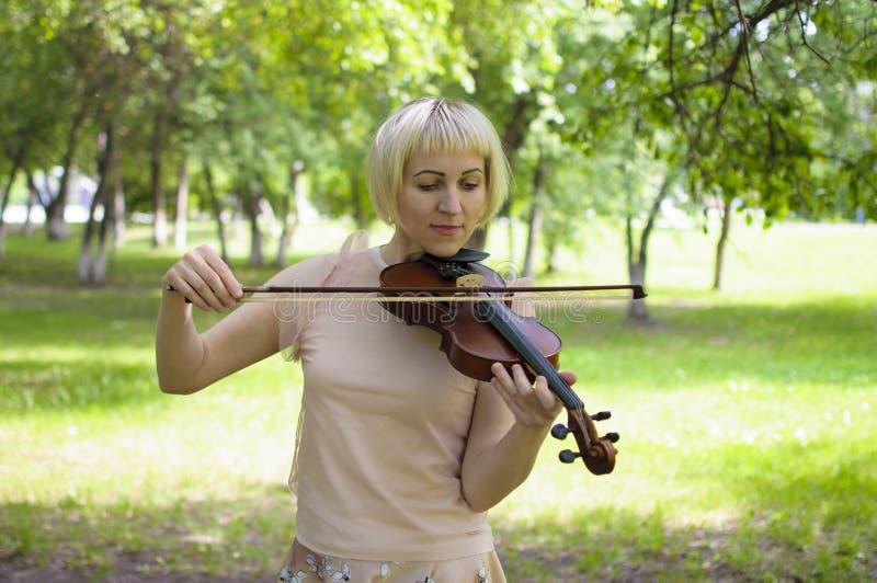 La femme russe joue un violon en parc pendant l'été image stock
