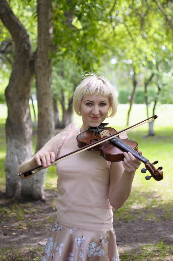 La femme russe joue un violon en parc pendant l'été photos libres de droits