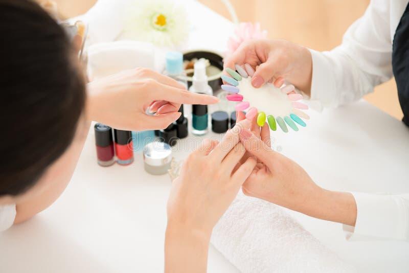 La femme sélectionne le vernis à ongles de gomme laque de couleur image libre de droits