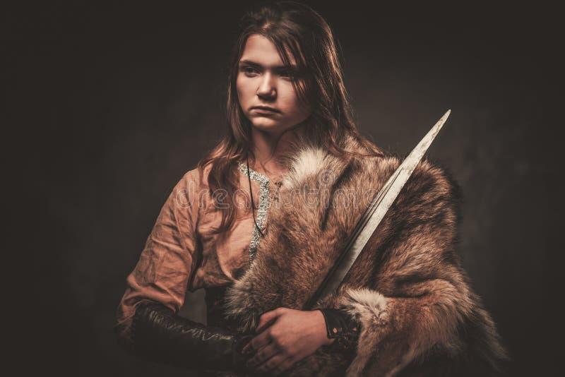 La femme sérieuse de Viking avec l'épée dans un guerrier traditionnel vêtx, posant sur un fond foncé photo libre de droits