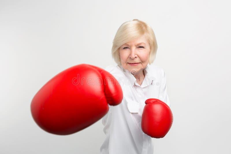 La femme sérieuse se tient en position, portant les gants de boxe rouges Elle est prête pour faire quelques exercices Sur images stock