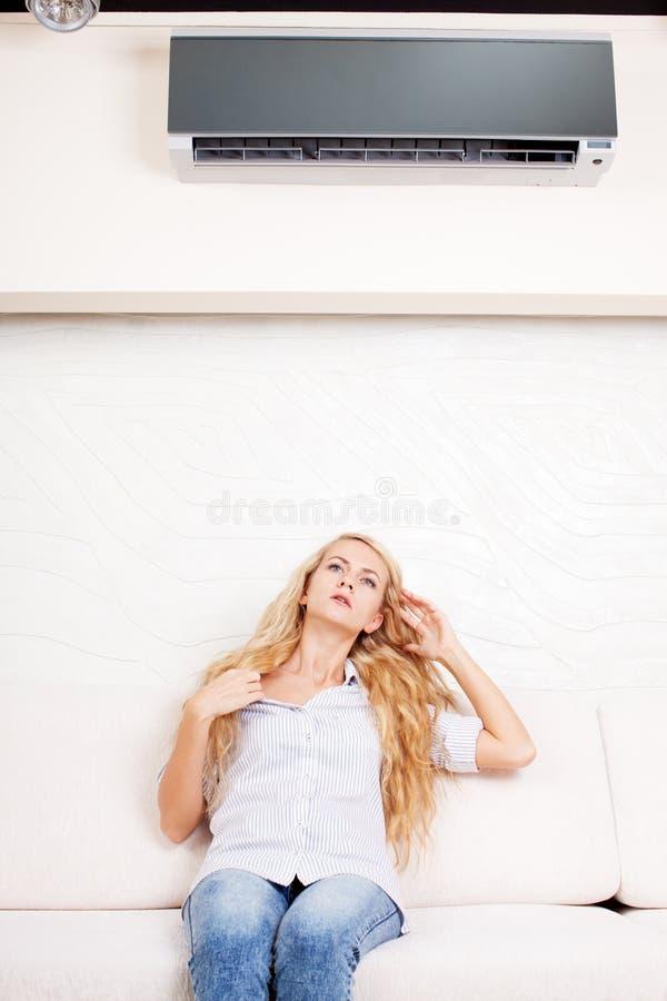 La femme s'échappe de la chaleur sous le climatiseur images libres de droits