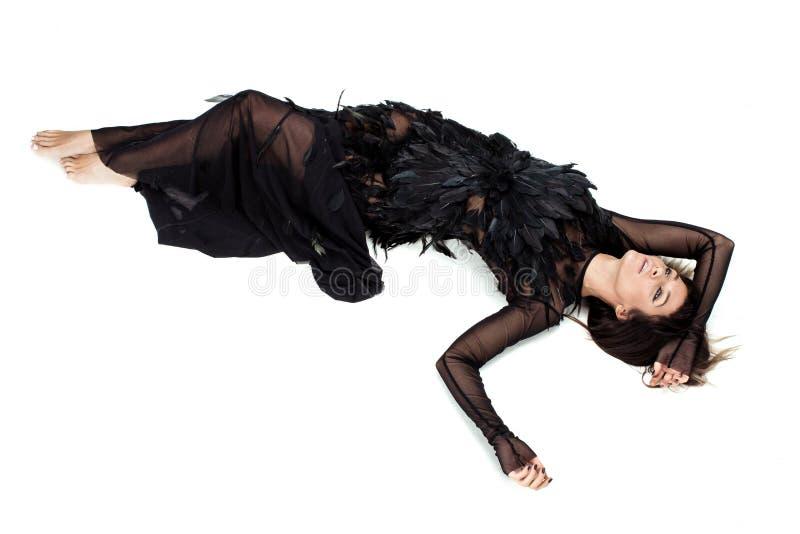 La femme s'étendant sur le plancher dans les plumes noires s'habillent images stock