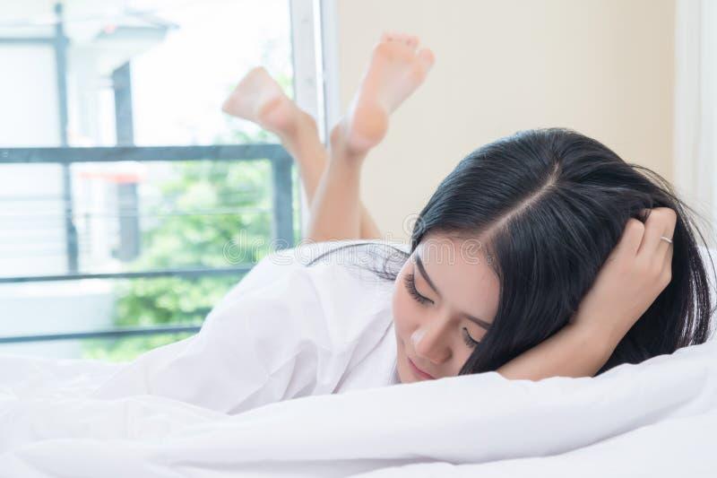 La femme s'étirant dans le lit après se réveillent Les femmes asiatiques sont éveillées dans le lit image stock