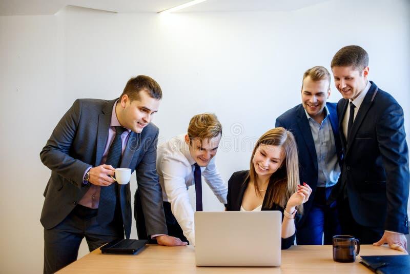La femme s'asseyant au bureau, l'équipe se tient autour de elle photos libres de droits