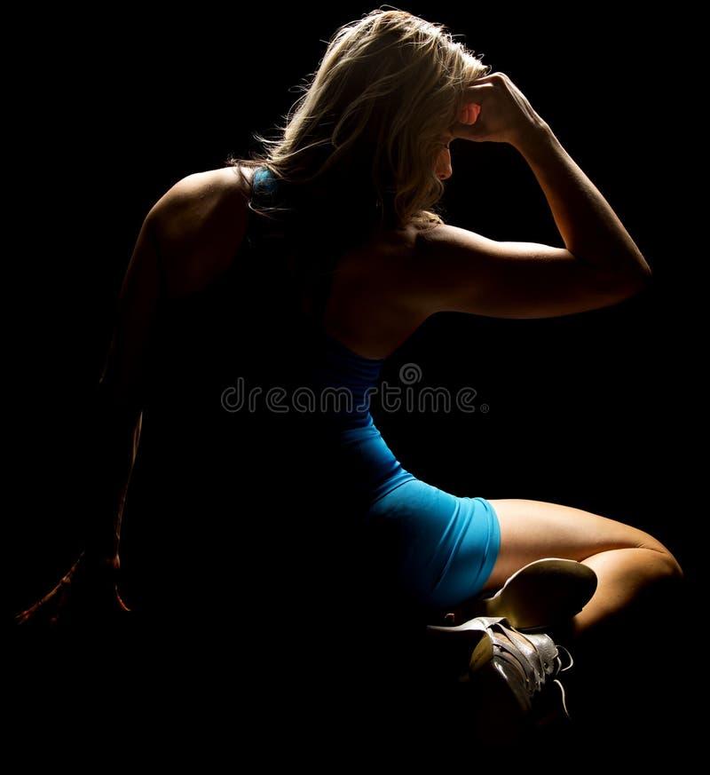 La femme s'asseyant dans l'équipement bleu highilighted du dos photographie stock libre de droits
