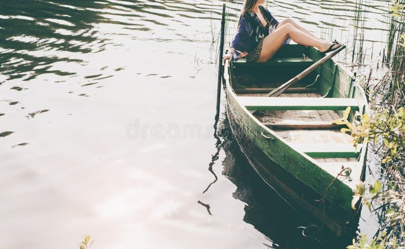 La femme s'asseyant dans le bateau et apprécient des moments de relaxation images libres de droits