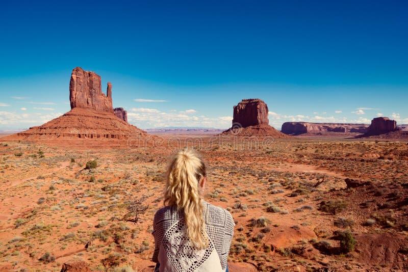 La femme s'asseyant en vallée de monument avec le rouge bascule l'aperçu photo stock