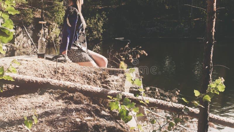 La femme s'asseyant sur la roche et apprécient des moments de relaxation photos stock