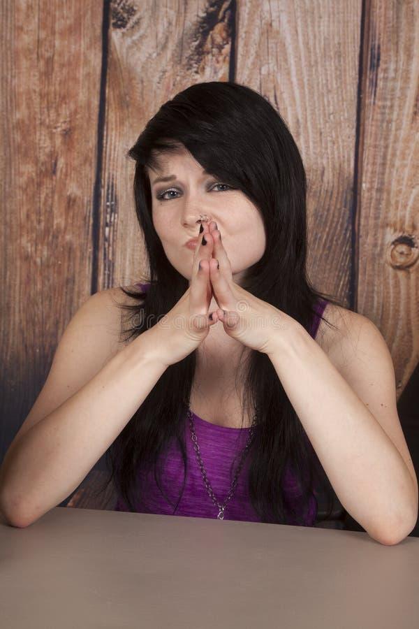 La femme s'asseyent en anneau de nez de bureau confus photo stock