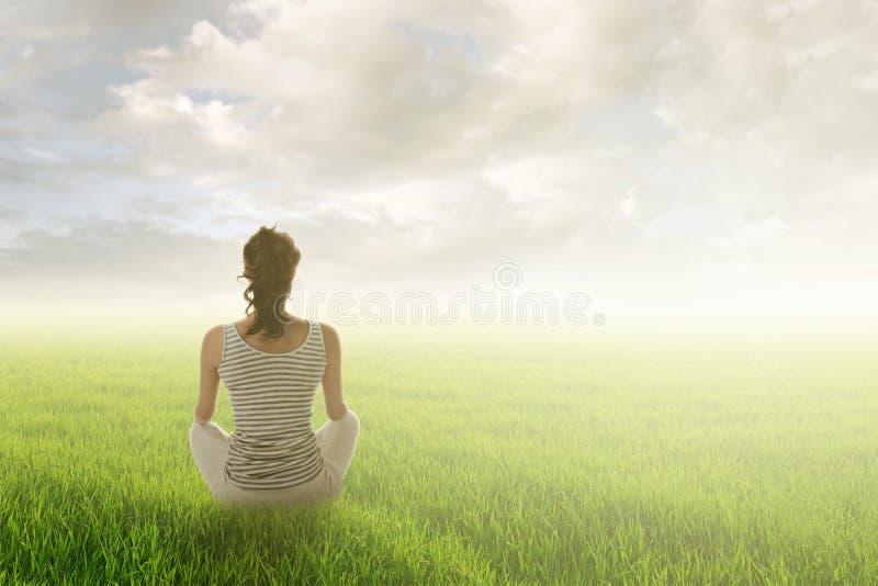 La femme s'asseyent sur la prairie photos stock