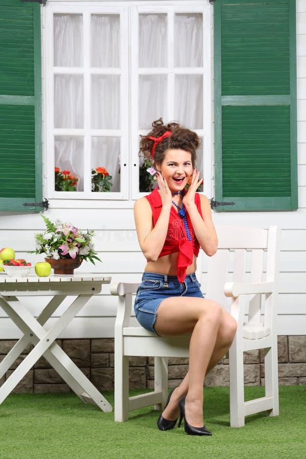 La femme s'assied à la table en bois blanche avec des fruits et des fleurs images stock