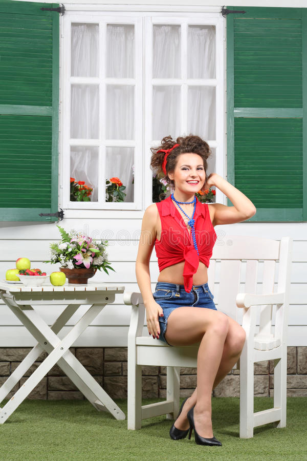 La femme s'assied à la table en bois blanche près de la maison avec des fenêtres images libres de droits