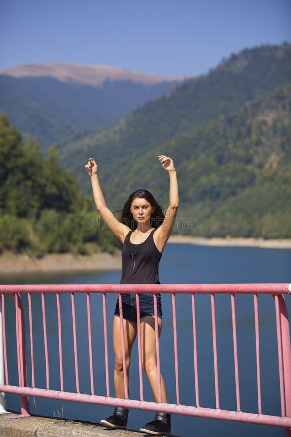 La femme s'assied au bord d'un barrage image stock