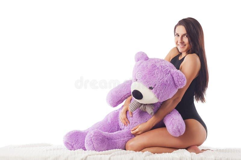 La femme s'assied dans le lit photos stock