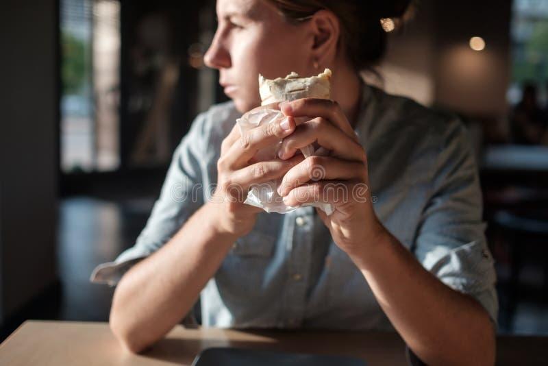 La femme s'assied en petit café et tient l'enveloppe de tortilla avant la consommation, regardant de côté images stock