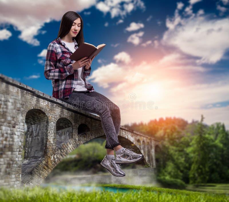 La femme s'assied sur le pont de pierre de voûte et lit le livre image stock