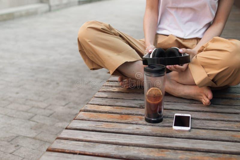 La femme s'assied sur un banc à côté d'une tasse de thé et tient des écouteurs Été image stock