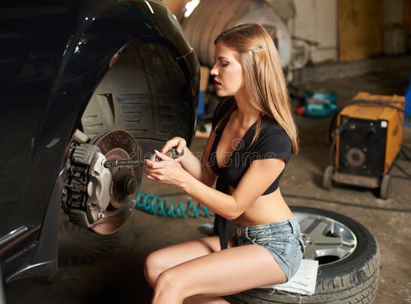 La femme s'est concentrée sur réparer le dispositif de direction d'une voiture noire image libre de droits
