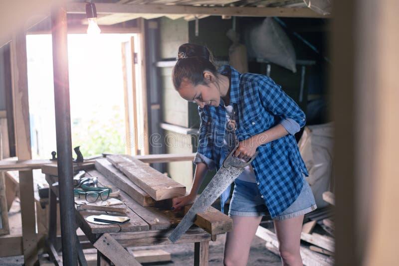 La femme s'est engagée en traitant le bois dans l'atelier à la maison, menuiserie photographie stock libre de droits