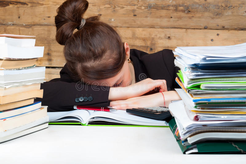 La femme s'est fatiguée du travail et de l'étude à côté de la pile photographie stock libre de droits