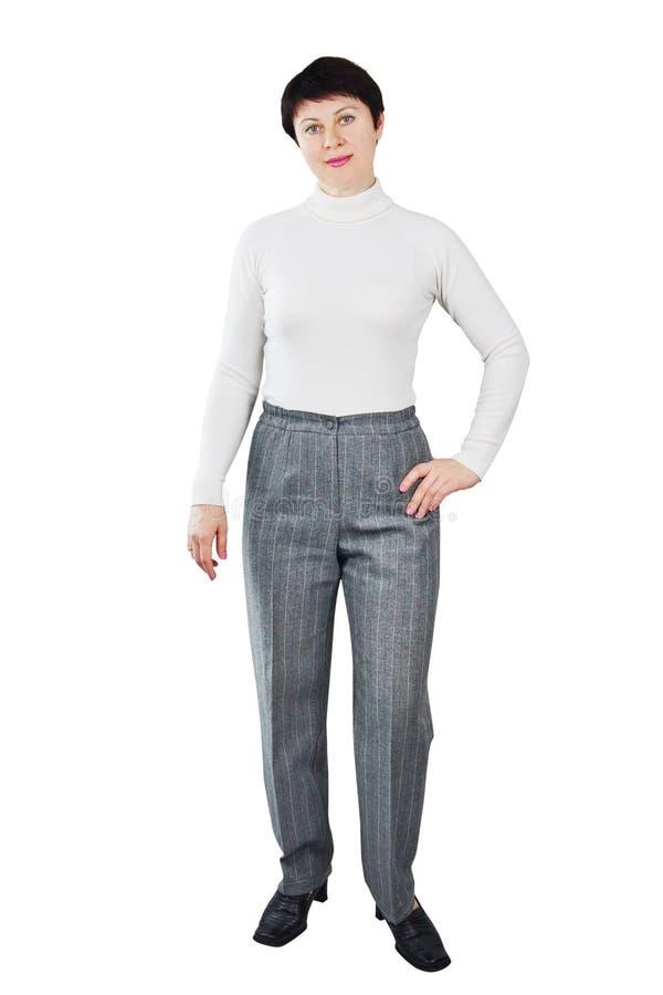 Femme habillée dans le col roulé blanc et le pantalon gris image libre de droits