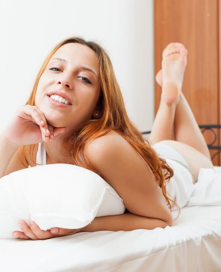 La femme s'est réveillée sur les feuilles blanches dans le lit à la maison photographie stock