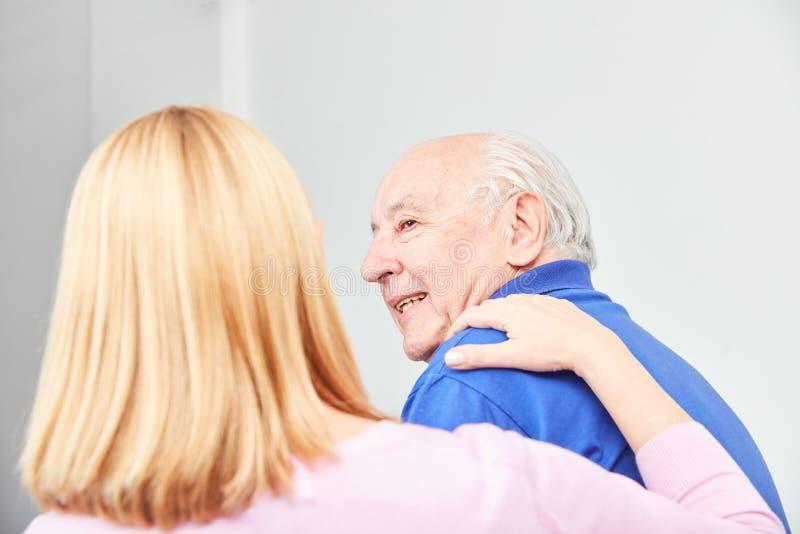 La femme s'occupe du vieil homme dans les soins à domicile photos stock
