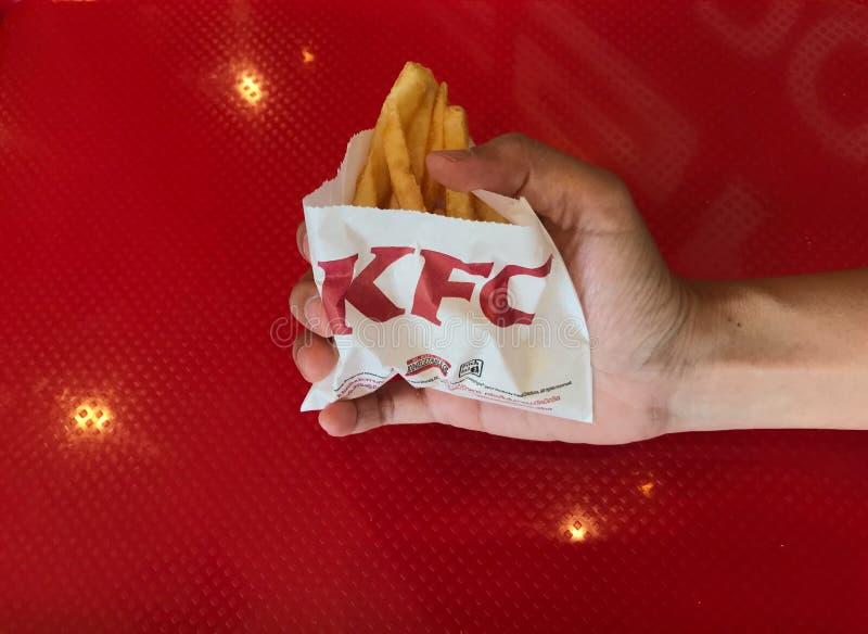 La femme saisit des pommes frites servant à KFC avec la table rouge sur le fond photo stock